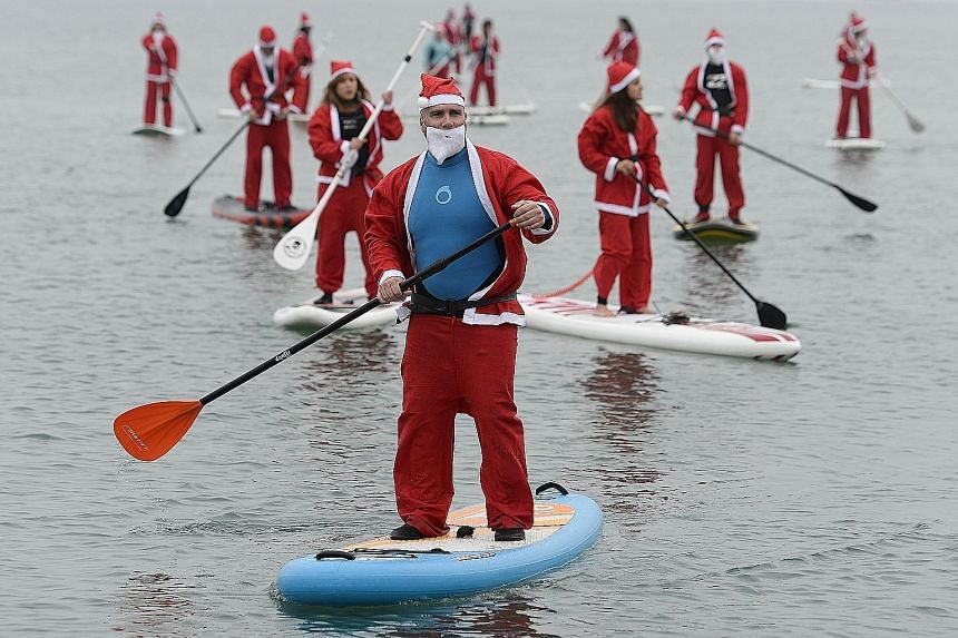 """(Above) """"Santas"""" riding on paddle boards for a fund-raiser off the beach in Barcelona on Sunday. (Above left) South Korean Ssenggom rock-climbing club members in the old familiar red suit scaling a rock face at a Christmas event on Saturday on Dobong"""