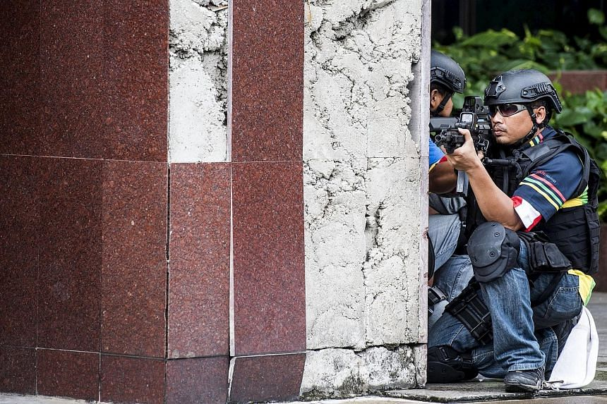 Police tape around a house (above) in Java raided by anti-terror forces on Sunday as Indonesia remains on high alert following the arrests of nine militants. Navy special forces (left) taking part in an anti-terror drill in Jakarta over the weekend.