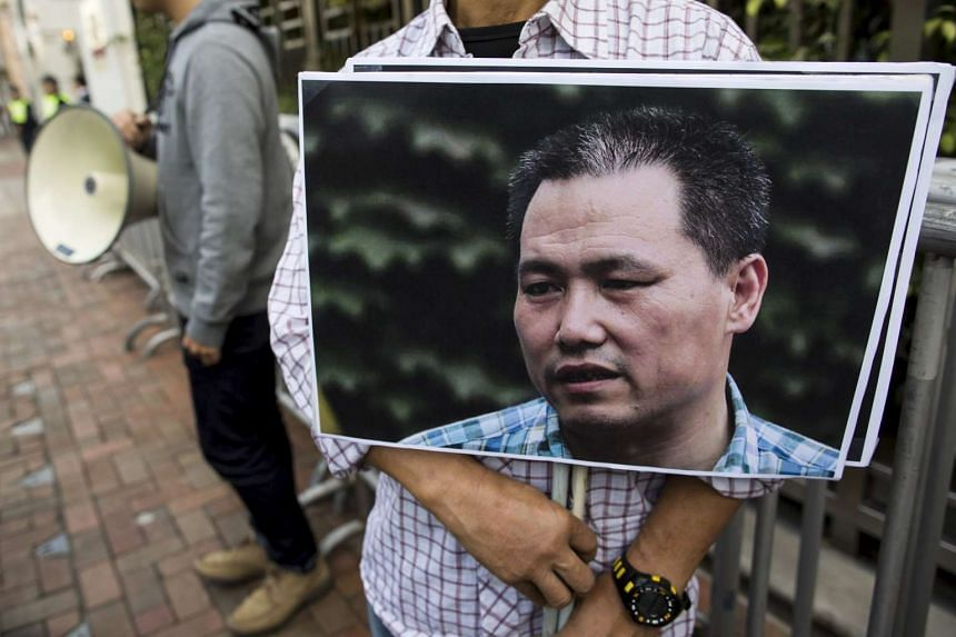 A pro-democracy protester holding a portrait of Chinese human rights lawyer Pu Zhiqiang, demanding his release during a demonstration, outside the Chinese liaison office in Hong Kong, China on Dec 15, 2015.