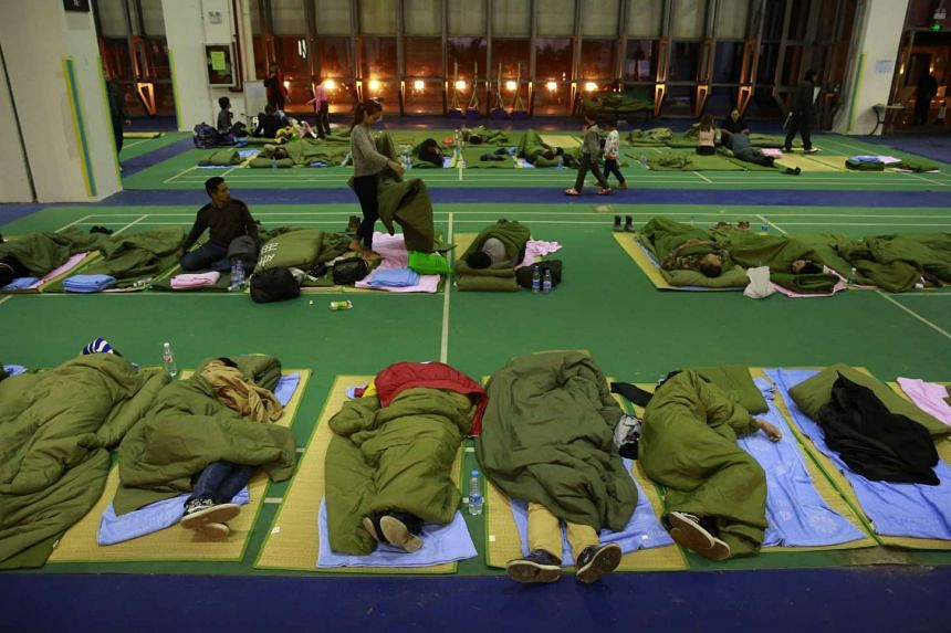 Evacuees sleep in a shelter set up at a gymnasium near the industrial park.