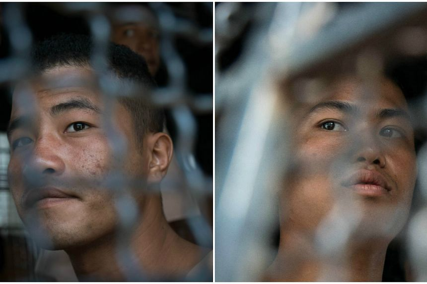 Myanmar nationals Zaw Lin (left) and Win Zaw Tun sitting in a prison transport van as they arrive at court for the start of his trial on the Thai resort island of Koh Samui on July 8, 2015.