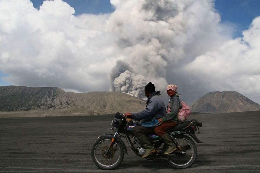 Villagers ride a motorbike past smoke and ash rising from the eruption of Mount Bromo in Probolinggo in eastern Java island on Dec 12, 2015.
