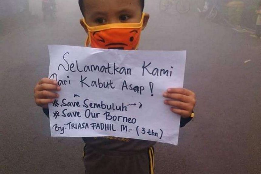 A child holds a sign asking for help to save them from the haze  Central Kalimantan on Borneo island last month.