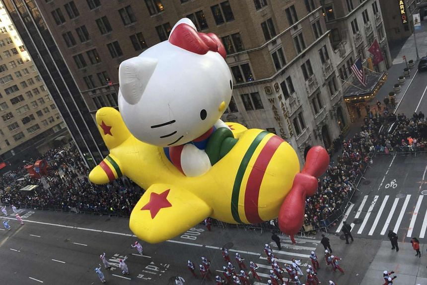 The Hello Kitty balloon proceeds high above spectators along 6th Ave during the 89th Macy's Thanksgiving Day Parade in Manhattan on Nov 26.