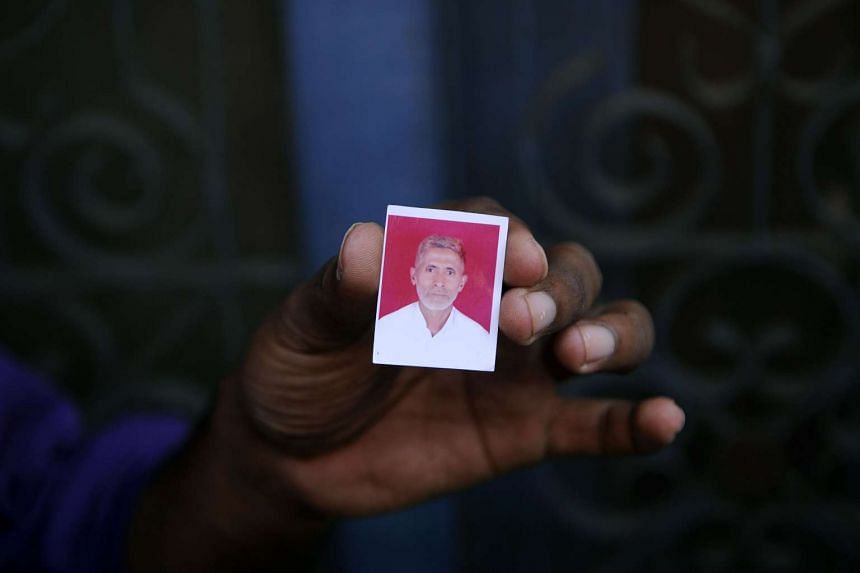 A relative holds a photograph of slain Indian villager Mohammad Akhlaq at his home in the village of Bisada.