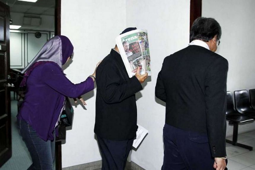Deputy Supt Rohaizat Abd Ani (centre) leaving the Section Court in Kota Kinabalu in 2013.