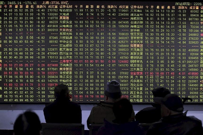 Investors looking at an electronic board showing stock information at a brokerage house in Hangzhou, Zhejiang province, China, on Nov 27, 2015.