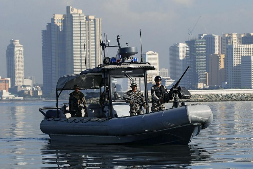 A Philippine Navy boat patrols Manila Bay overlooking the Manila skyline as a security preparation for Asia-Pacific Economic Cooperation meeting.