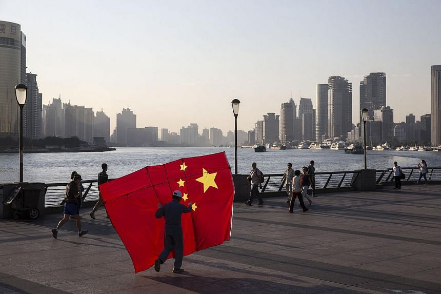 A man carrying a kite in the shape of the Chinese national flag, walks along the Bund in Shanghai, China, on Oct 2, 2015.