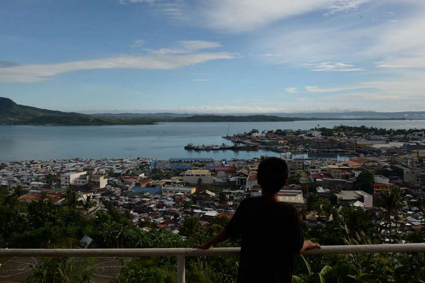 A young boy looking at Tacloban City central Philippines, ahead of the two-year anniversary of the devastating typhoon Haiyan.