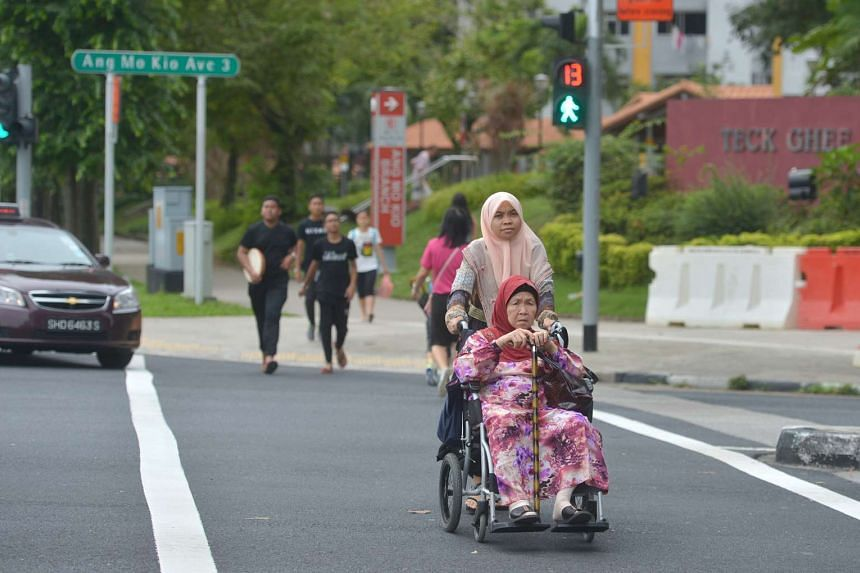 A woman pushing an elderly person on a wheelchair across the road.