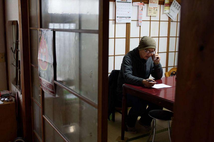 Mr Akihiro Takano speaking on the telephone in Saitama City, Saitama Prefecture, Japan, on Dec 14, 2015.