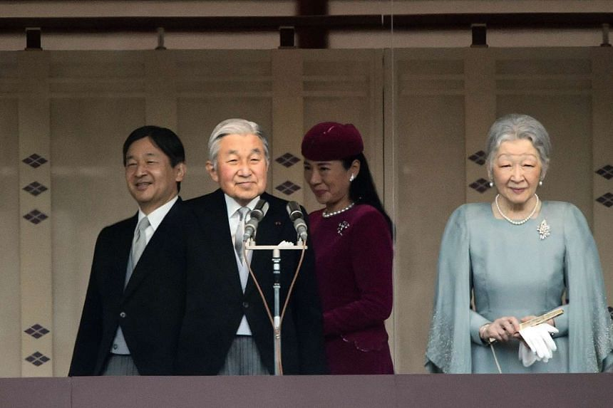 Japanese Emperor Akihito (second, left) and Empress Michiko (right) greeting the crowd as Crown Prince Naruhito (left) and Crown Princess Masako (second, right) walk behind on the balcony of the Imperial Palace in Tokyo on Dec 23, 2015.