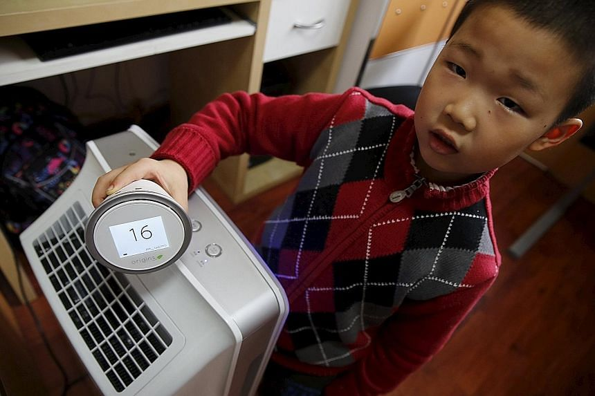 A boy with a portable device that measures air quality and an air purifier in his home in Beijing on Sunday. Beijing has issued its second red alert for smog this winter, leading to the closure of schools and factories.