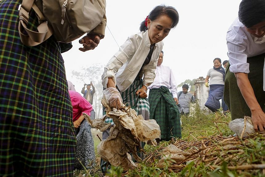Ms Aung San Suu Kyi helping to pick up litter during a clean-up drive in Kawhmu township, on the outskirts of Yangon, on Dec 13. The exercise has been described by her party as bringing change through acts of individual responsibility.