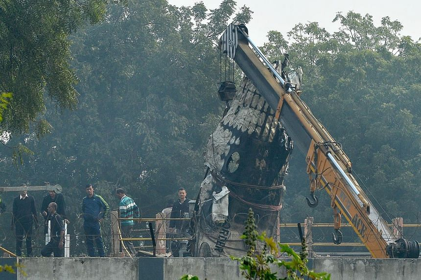 A piece of wreckage being hoisted by a crane after a plane crash yesterday morning near New Delhi's main airport. A chartered Indian aircraft carrying military personnel exploded in a fireball and killed all 10 people on board after crashing into a w
