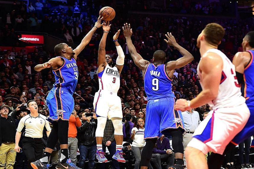 Chris Paul (No. 3) of the Los Angeles Clippers having his last-second shot blocked by Kevin Durant (left) of the Oklahoma City Thunder, resulting in a narrow 100-99 Thunder victory. The Thunder have now won eight of their past nine games, while the C