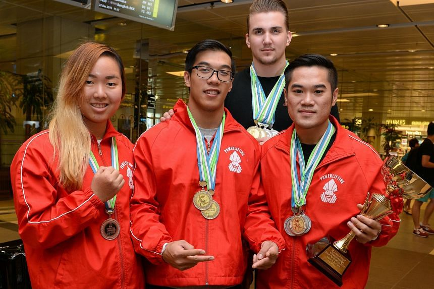 The successful Singapore contingent - (from left) Alina Choo, Christophe Ang, Daniel Nobel and Clinton Lee - displaying their medals as they arrived home yesterday morning. The fifth member, Derrick Kim, came back a day earlier.