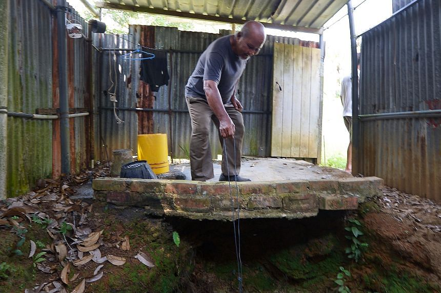 Pulau Ubin resident Ahmad Kassim drawing water from a well opposite his home, which he claims is still safe to drink. Despite warnings from the authorities that water on the island should not be drunk without being boiled first, the 80-year-old was s