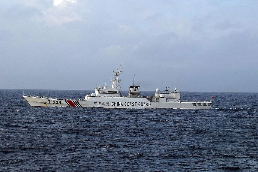 "A Chinese coast guard ship armed with ""cannon-like"" weapons near disputed islets in a photograph released by Japan yesterday."