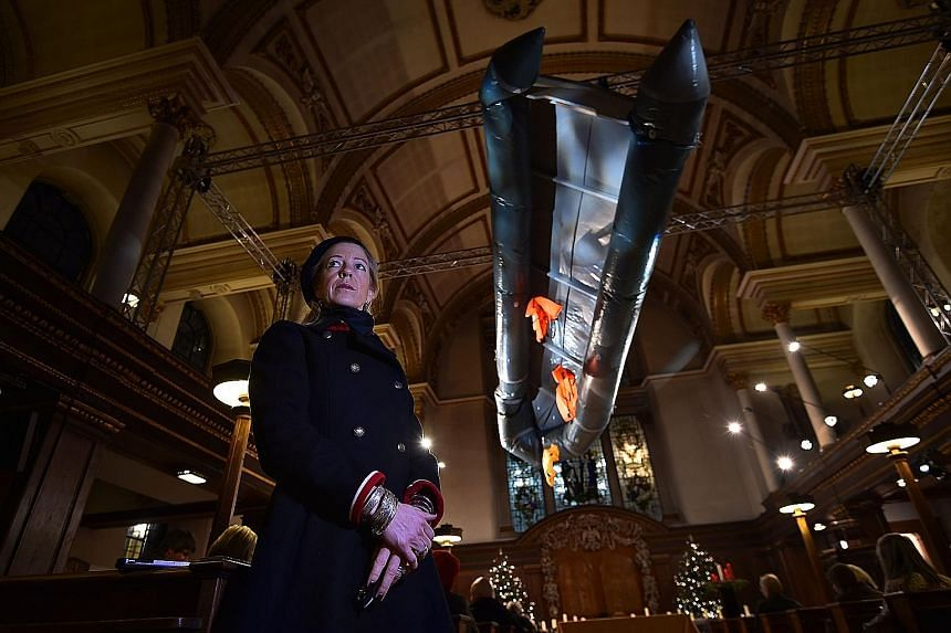 British artist Arabella Dorman in St James's Church, London, with her piece representing a capsized refugee boat. Migrant groups have expressed worry over anti-refugee policies.
