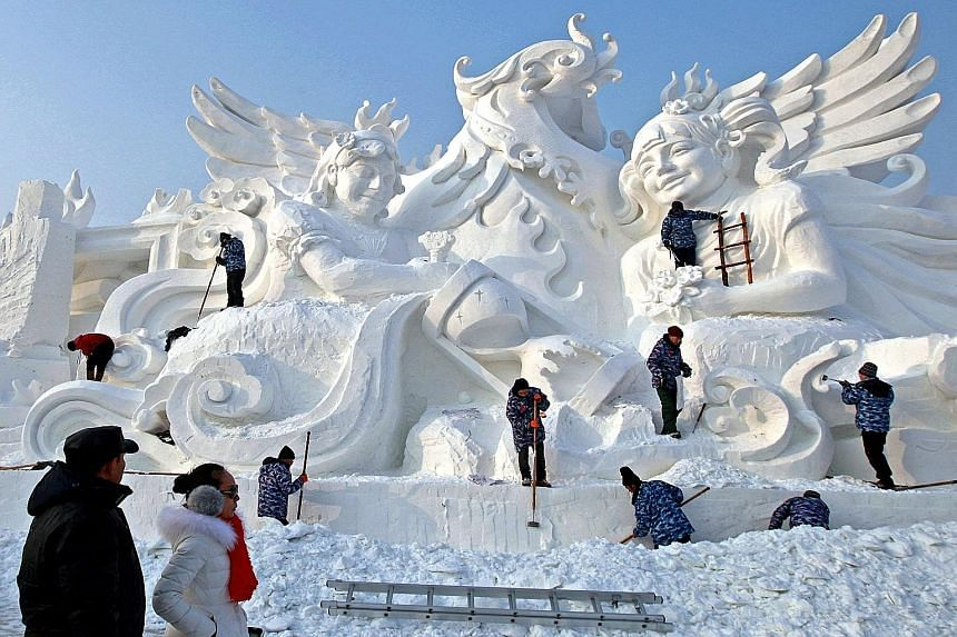 Artists chiselling away at a snow sculpture, which resembles a traditional marble work of art, at the annual International Snow Sculpture Art Expo in Harbin, Heilongjiang province, in China yesterday. Spectacular frozen works can be seen at this larg