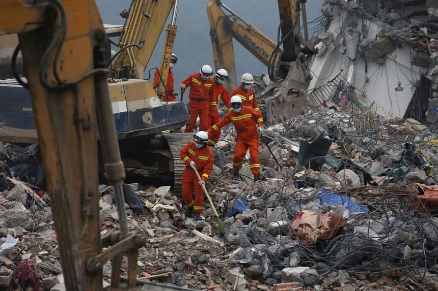 Rescue workers near a damaged house in the industrial park hit by a landslide in Shenzhen.