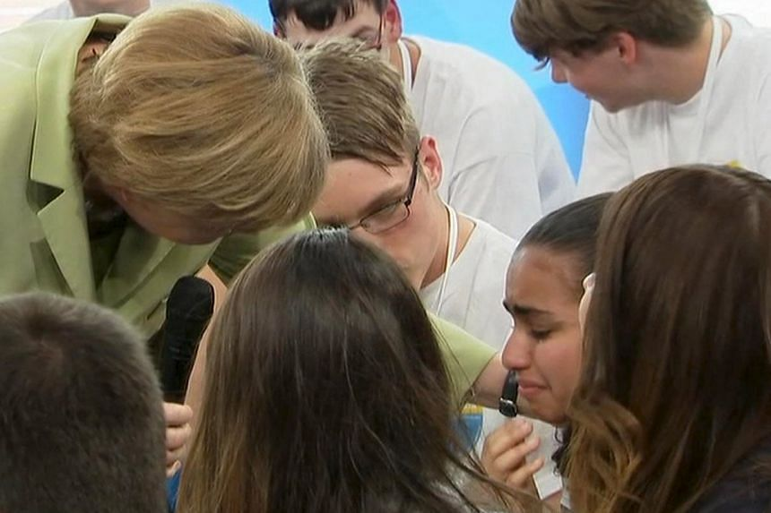 German Chancellor Angela Merkel (left) comforting crying Palestinian girl Reem Sahwil during a televised forum in Rostock, Germany, on July 15, 2015.