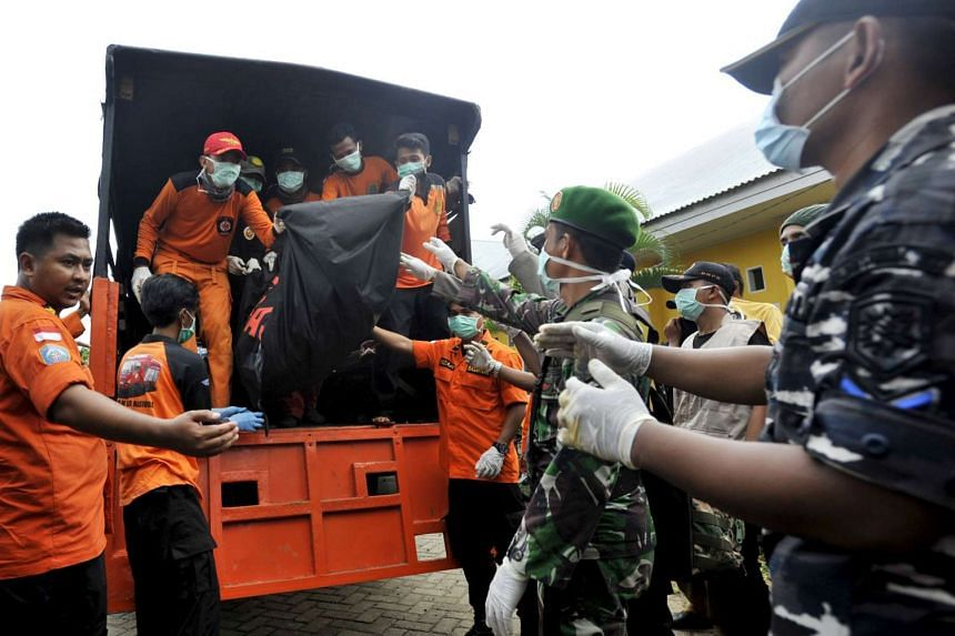 Rescue team members and soldiers unloading the body of a victim at Shiva hospital in Wajo, South Sulawesi province, on Dec 23, 2015.