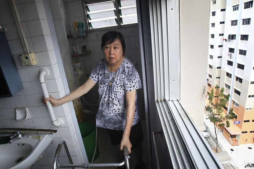 Madam Eng Bok Hua, 70, holds on to the grab bars while making her way out of the toilet of her HDB flat.