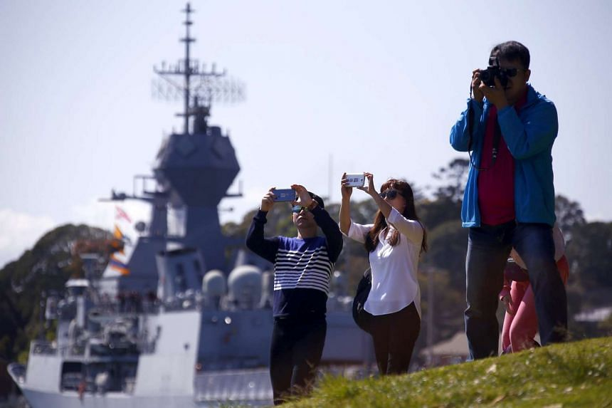 Chinese tourists stand in front of an Australian naval ship as they take pictures of the Sydney Opera House and Harbour Bridge.
