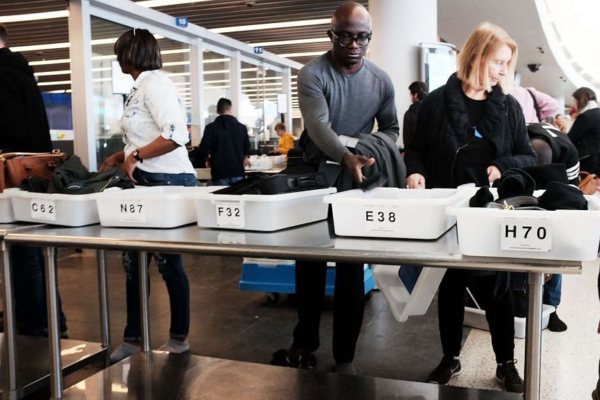 People go through a security check at JFK Airport.