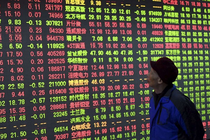 An investor looks at an electronic board showing stock information at a brokerage house in Hangzhou, China.