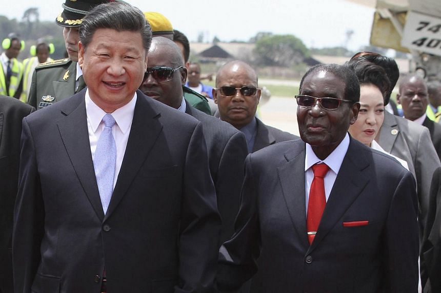 Chinese President Xi Jinping (left) with Zimbabwean President Robert Mugabe (right) during a state visit in Harare, Zimbabwe on Dec 1, 2015.