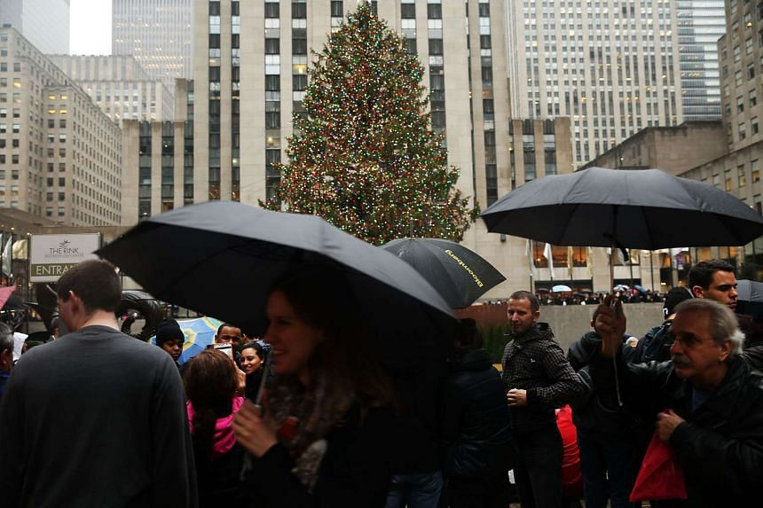 People walk past the Christmas tree at Rockefeller Centre on Dec 22, 2015 in New York City.