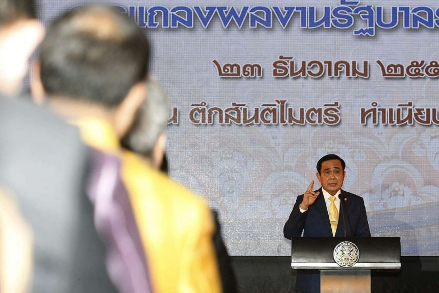 Thai Prime Minister Prayut Chan-o-cha (right) speak as he delivers the one-year performance presentation of his government at Government House in Bangkok, Thailand.