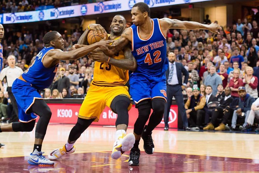 Langston Galloway #2 and Lance Thomas #42 of the New York Knicks trying to stop LeBron James #23 of the Cleveland Cavaliers during the second half at Quicken Loans Arena on December 23, 2015.