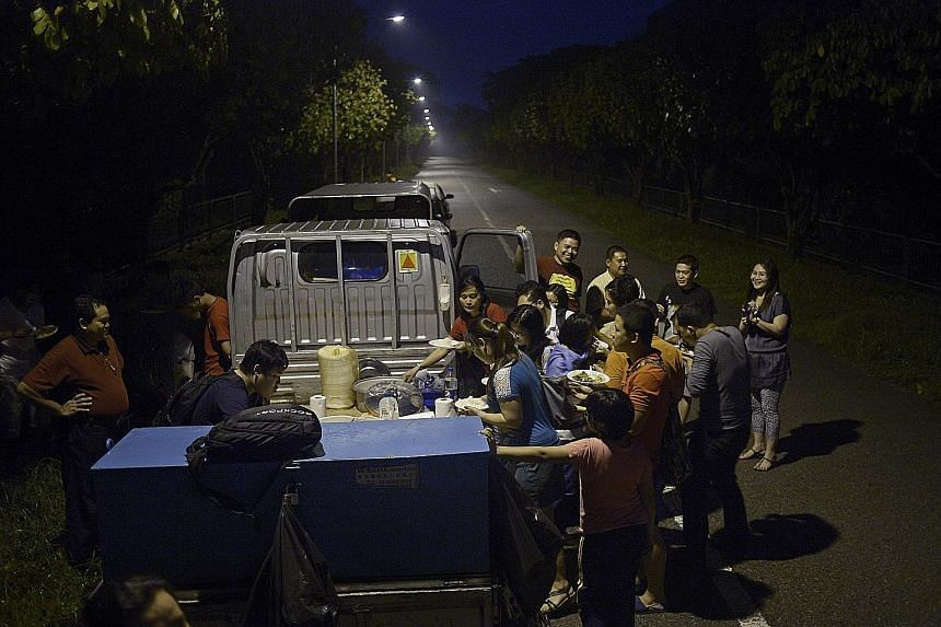 Workers from a chicken farm in the Lim Chu Kang area tucking into traditional Myanmar and Karen fare such as beef curry and braised eel, provided by Karen Baptist Church members.