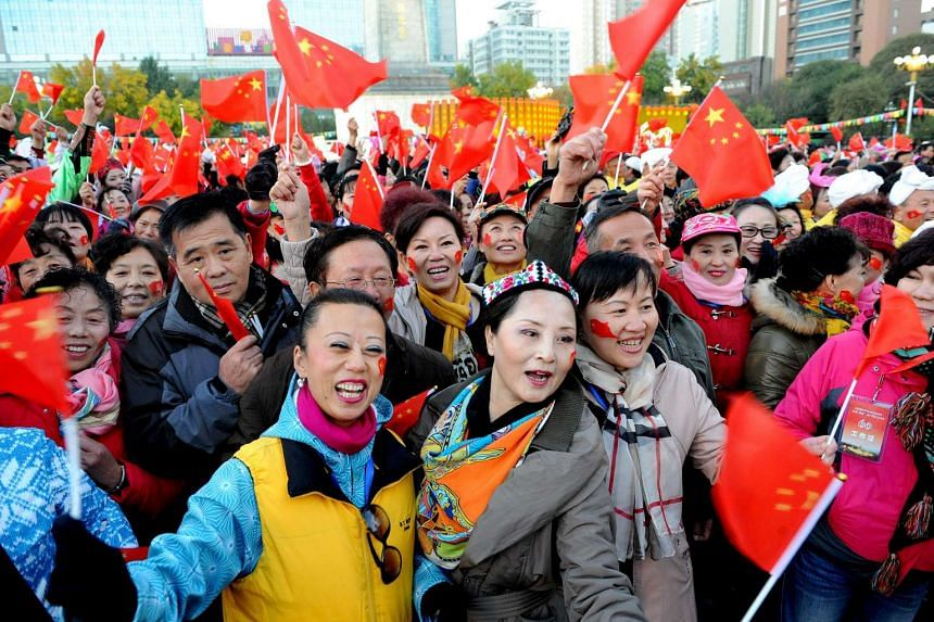 People holding Chinese national flags during a celebration to mark the 60th anniversary of the founding of the Xinjiang Uighur Autonomous Region, in Urumqi on Oct 1, 2015.