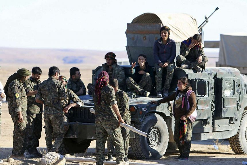 Fighters from the Syrian Democratic Forces gathering around the al-Khatoniyah lake area after they took control of it from ISIS, on Nov 14, 2015.