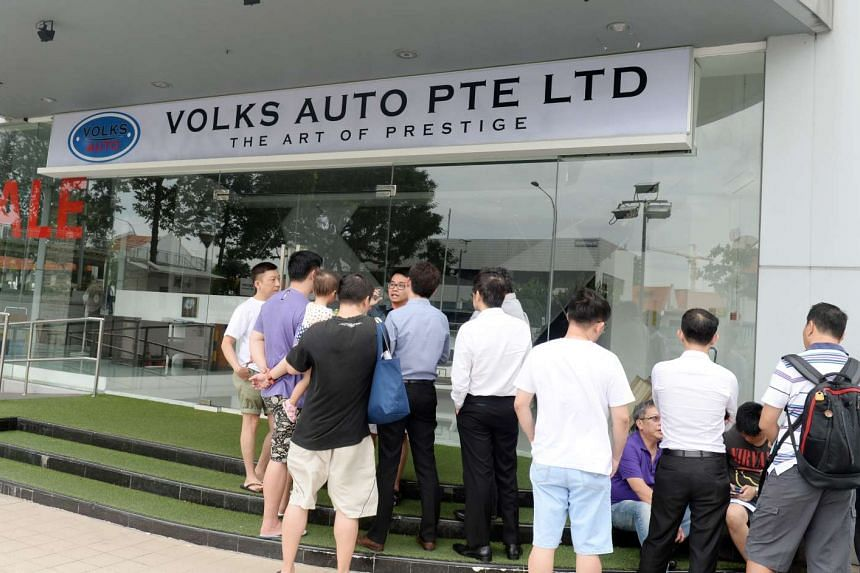 People gathering outside Volks Auto, a car dealership in MacPherson Road, after they said that cars they purchased from the dealership had not been delivered.