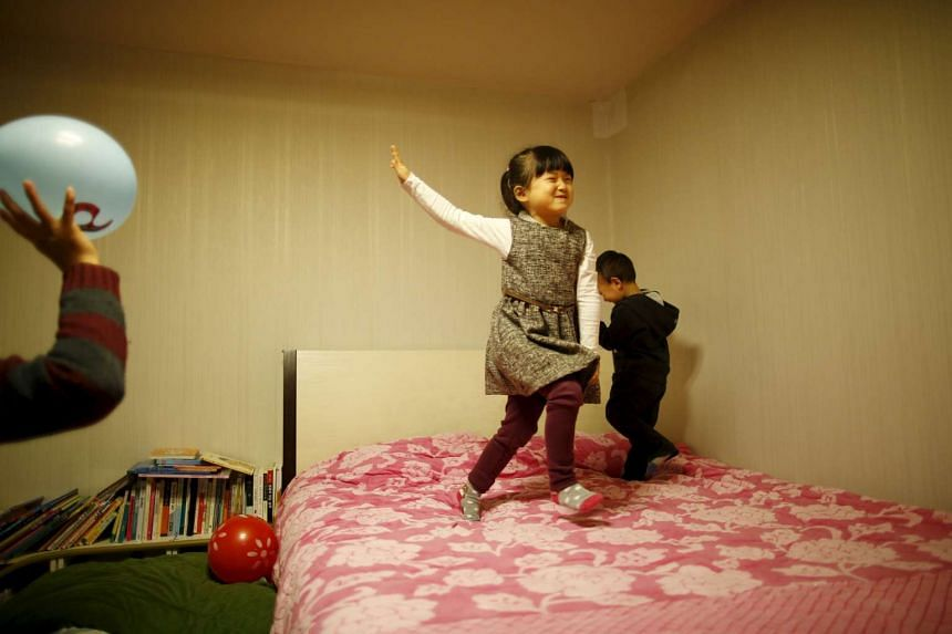 Chung So-yool (centre) and Chung Young-joon play with their father at their apartment in Seoul on, Dec 16.
