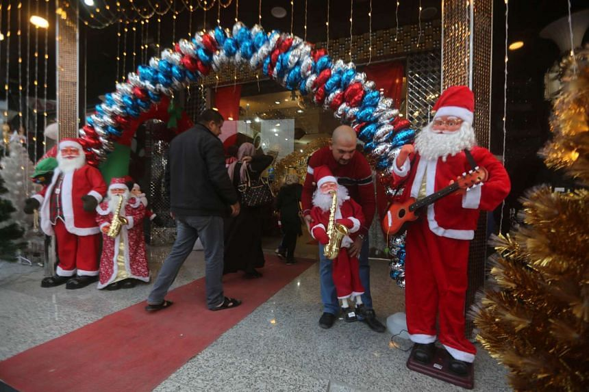 An Iraqi man displays a Santa Claus outside a shop in central Baghdad's Karada district on Dec 18, ahead of Christmas celebrations.