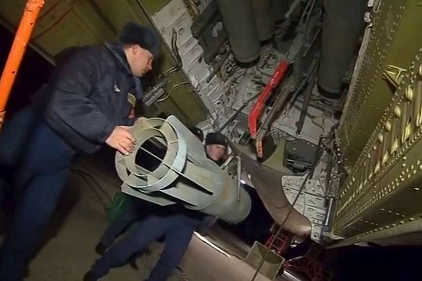 Russian ground staff members load a long-range bomber with weapons at the Hmeymim air base near Latakia, Syria.