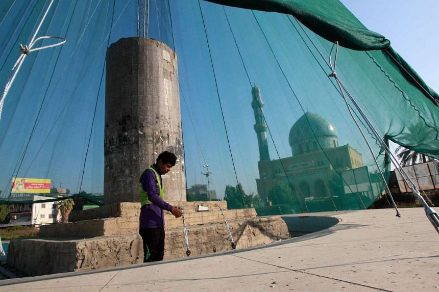 A worker installs a giant Christmas tree in front of Baghdad's landmark Ramdan 17 mosque in the Iraqi capital's Firdous Square on Monday.