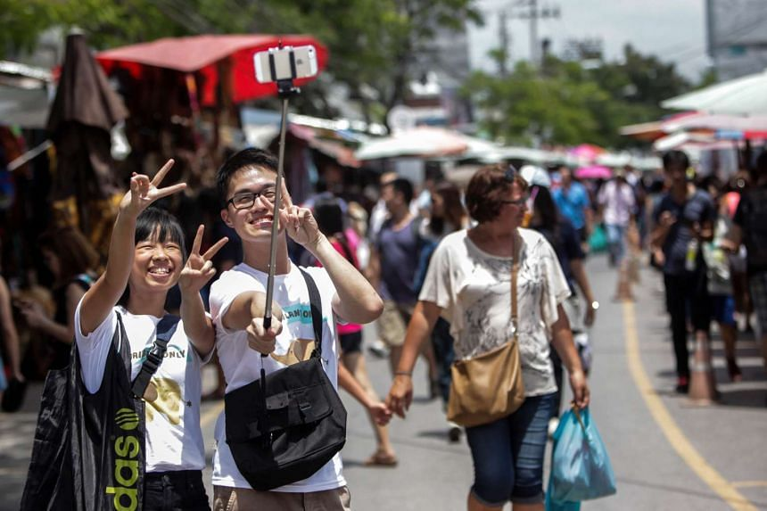 "Tourists pose for a ""selfie"" photograph at the Chatuchak market in Bangkok, Thailand, Jun 28, 2014."
