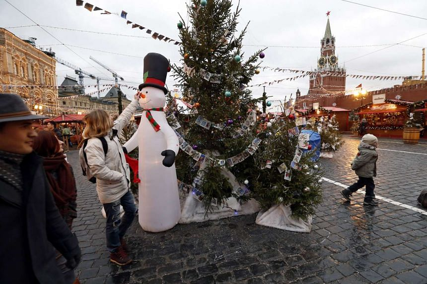 A person tweaking a snowman's carrot nose on Red Square in Moscow on Dec 23, 2015.