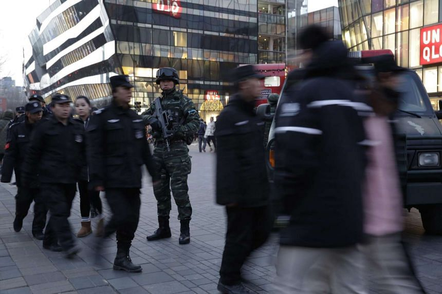 Armed Chinese paramilitary police stand guard outside a shopping mall in Sanlitun area on Christmas eve in Beijing, China, Dec 24, 2015.