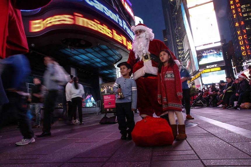 A man dressed as Santa Claus greets people in Times Square on Dec 24, 2015, in New York City.