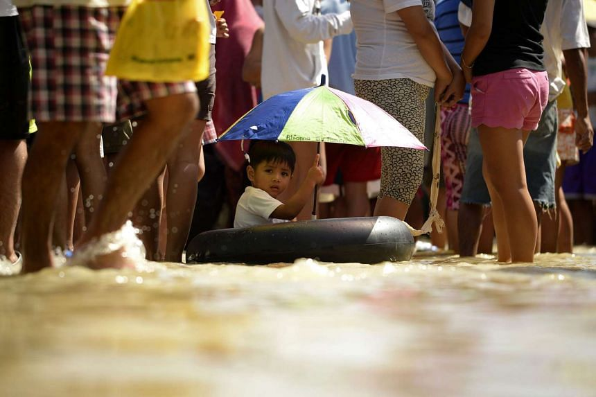 A child sits in a flotation device as residents queue up in flood waters to receive relief goods in Calumpit Bulacan, north of Manila.